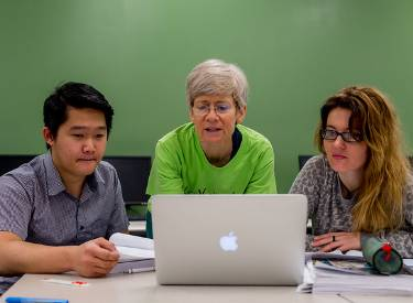 Photo of an LWTech female faculty helping two students