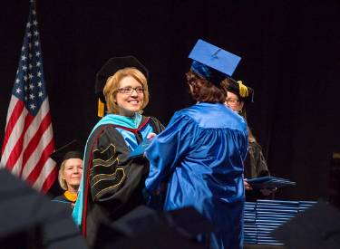 LWTech President Amy Morrison shaking hands with an LWTech graduate