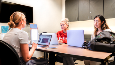 Three students studying together at a table in Study Room A
