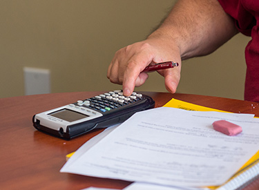 Student working out financial calculations on a calculator