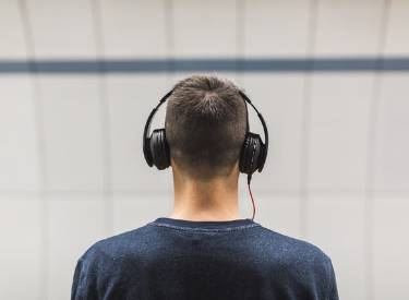 Back of a man with headphones over his ears
